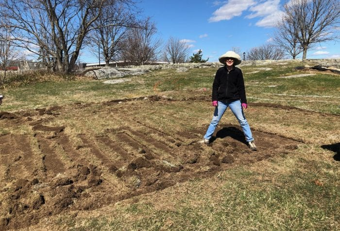 Mary gladly takes a photo op break from rolling sod.