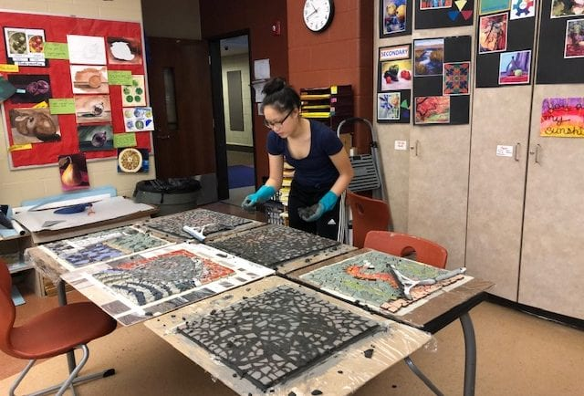 Addie moving on to grout the next mosaic