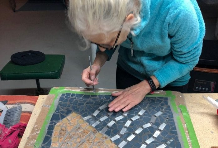 Mary putting the finishing touches on a jellyfish mosaic.