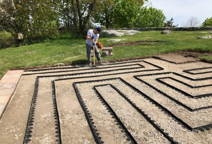 Jeff hand-tamps any aggregate that was loosened during the edging process. Now ready for Coast Guard volunteers to help carry pavers over!